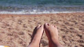Os pés encontram-se em um vadio do sol na praia video estoque