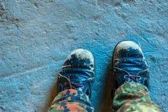 Os pés envolvidos em sapatas velhas estão na estrada foto de stock