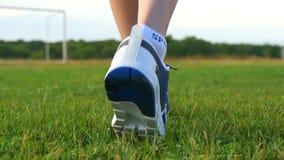 Os pés fêmeas do close-up nas sapatilhas estão andando em um close-up verde do gramado Esporte e atividades exteriores vídeos de arquivo