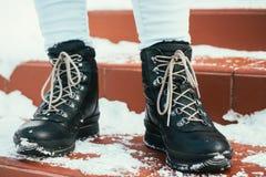 Os pés fêmeas em botas do inverno com laços estão nas escadas no Imagem de Stock Royalty Free