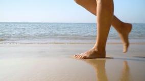 Os pés fêmeas fecham-se acima Pés e pés da mulher que andam na praia Ressaca do oceano Console tropical Mothion lento filme