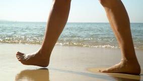 Os pés fêmeas fecham-se acima A mulher feliz vai perto das ondas de oceano Ressaca do oceano Console tropical Mothion lento vídeos de arquivo