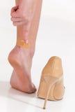 os pés fêmeas na dor após ter vestido a elevação colocaram saltos sapatas Fotografia de Stock