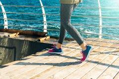 Os pés fêmeas nas sapatilhas correm abaixo das escadas na praia no Fotografia de Stock