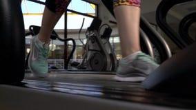 Os pés fêmeas nas sapatilhas running estão correndo em uma escada rolante no gym, movimento lento video estoque