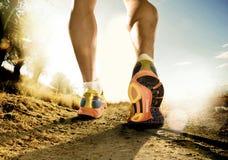 Os pés fortes e as sapatas do homem do esporte que movimentam-se no treinamento da aptidão malham fora da estrada