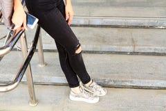 Os pés longos do ` s da mulher em calças de brim pretas arfam Imagens de Stock