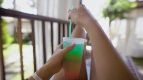 Os pés magros e a mão da mulher bronzeada estão guardando de vidro com o cocktail com palha, mulher estão encontrando-se em uma c filme