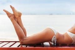 Os pés magros novos bonitos da mulher tomam sol na praia Fotografia de Stock Royalty Free