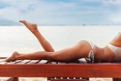Os pés magros novos bonitos da mulher tomam sol na praia Fotos de Stock