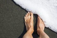 Os pés masculinos na areia vulcânica preta cobrem com a espuma do mar branco minimalism geométrico diagonal foto de stock royalty free
