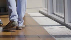 Os pés masculinos põem sobre calças azuis à moda e as sapatas marrons do verão andam no assoalho filme