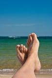Os pés na areia de encontro ao mar Fotos de Stock