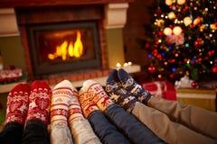 Os pés nas lãs golpeiam perto da chaminé no inverno Imagem de Stock