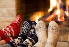 Os pés nas lãs golpeiam perto da chaminé no tempo de inverno fotografia de stock