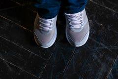 Os pés nas sapatilhas brancas estão no assoalho de parquet preto fotos de stock royalty free