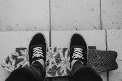 Os pés nas sapatilhas pretas em um patim embarcam Foto de Stock Royalty Free