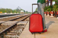Os pés ocasionais do turista do viajante estão na estrada de ferro com uma mala de viagem vermelha Imagens de Stock