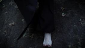 Os pés pálidos desencapados da mulher estão vestindo o revestimento preto longo, andando na floresta no outono sobre a terra molh vídeos de arquivo