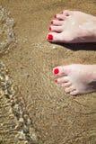 Os pés pedicured da mulher com verniz para as unhas vermelho nos dedos do pé na areia na água foto de stock