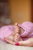 Os pés recém-nascidos nas mãos delicadas da mãe Fotografia de Stock Royalty Free
