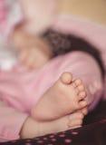 Os pés recém-nascidos nas mãos delicadas da mãe Imagens de Stock Royalty Free
