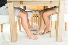 Os pés sob a tabela - jogos sujos do homem e da mulher fotografia de stock