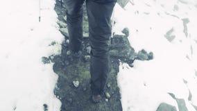 Os pés vão acima do monte nas rochas Fugas em torno da neve lama as sapatas do video estoque