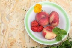 Os pêssegos e a morango maduros que encontram-se em uma placa Imagens de Stock