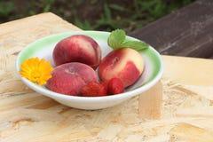 Os pêssegos e a morango maduros que encontram-se em uma placa Fotografia de Stock