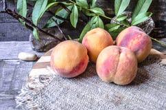 Os pêssegos maduros com um ramo em uma placa de corte cobriram o pano de saco Fotografia de Stock