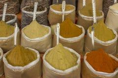 Os pós coloridos brilhantes das especiarias nos sacos com colheres estão no contador imagens de stock