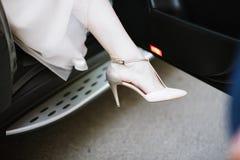Os p?s da noiva em um vestido de casamento nas sapatas fotografia de stock