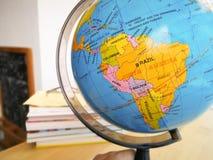 Os países e os continentes fecham-se acima com o mapa de cor em um globo com os livros no fundo imagens de stock