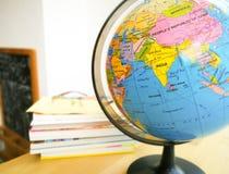 Os países e os continentes fecham-se acima com o mapa de cor em um globo com os livros no fundo foto de stock royalty free