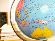 Os países e os continentes fecham-se acima com o mapa de cor em um globo com os livros no fundo fotos de stock