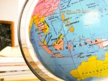Os países e os continentes fecham-se acima com o mapa de cor em um globo com os livros no fundo fotografia de stock