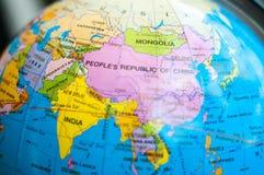 Os países e os continentes fecham-se acima com o mapa de cor em um globo com os livros no fundo fotos de stock royalty free