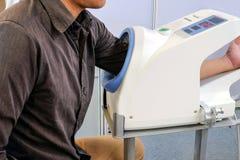 Os pacientes masculinos introduzem seu braço esquerdo no monitor da pressão Fotografia de Stock