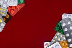 Os pacotes das tabuletas são ficados situados em um fundo vermelho com um lugar imagens de stock royalty free