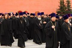 Os padres vão na cerimónia da grinalda que coloca no túmulo Fotos de Stock Royalty Free