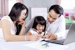 Os pais ajudam sua filha que faz trabalhos de casa Foto de Stock Royalty Free