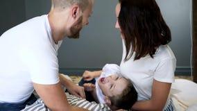Os pais alegres com filho têm o tempo do divertimento na cama em casa no quarto, momentos felizes video estoque
