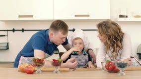 Os pais alimentam seu filho com as morangos na cozinha Estão preparando o café da manhã filme