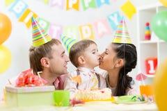 Os pais beijam seu filho que comemora o aniversário da criança fotos de stock