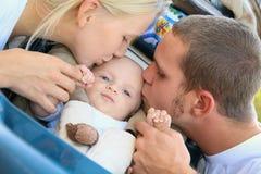 Os pais caucasianos encantadores beijam seu filho do bebê Imagens de Stock Royalty Free