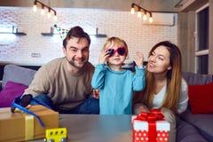 Os pais com bolo de aniversário felicitam sua criança foto de stock