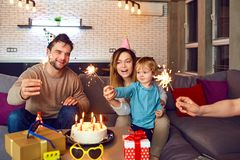 Os pais com bolo de aniversário felicitam sua criança imagem de stock