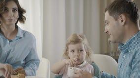Os pais com a criança comem sobremesas e bebem o chá, criança da ajuda dos adultos video estoque