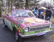 Os pais com crianças exploram um carro colorido velho Imagens de Stock Royalty Free